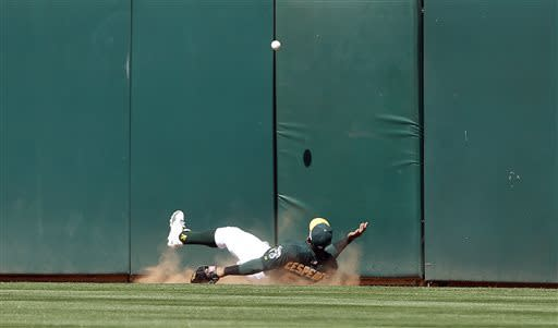 Oakland Athletics left fielder Yoenis Cespedes falls under a triple hit by Los Angeles Angels' Mike Trout during the eighth inning of a baseball game in Oakland, Calif., Wednesday, May 1, 2013. (AP Photo/Jeff Chiu)