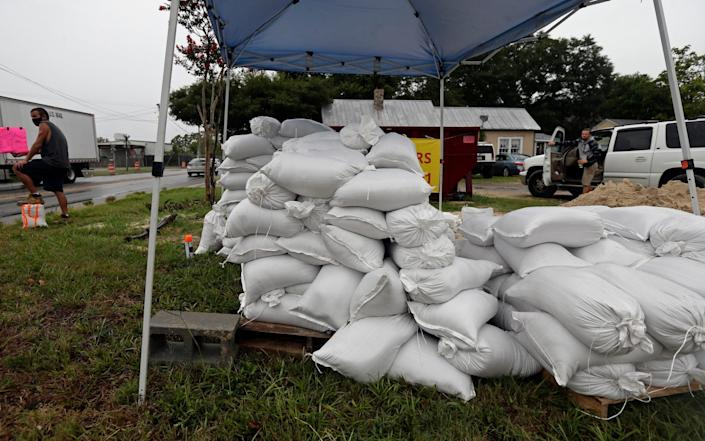 A man sells sand bags in Wilmington, North Carolina as residents braced for the arrival of Hurricane Isaias - Gerry Broome/AP
