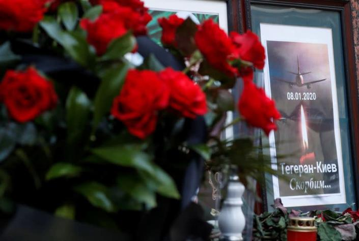 Flowers and a memorial poster are placed outside the Iranian Embassy to commemorate the victims of the Ukraine International Airlines flight PS752 plane crash