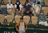 Spain's Alejandro Davidovich Fokina reacts after missing a shot as he is watched by mask wearing spectators, in his match against Argentina's Federico Delbonis in the fourth round match on day 8, of the French Open tennis tournament at Roland Garros in Paris, France, Sunday, June 6, 2021. (AP Photo/Christophe Ena)