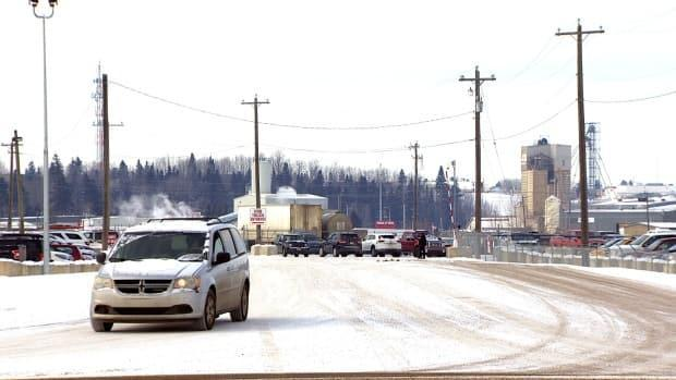 A vehicle pulls out of the parking lot at the Olymel pork plant in Red Deer, Alta. The plant has temporarily shut down due to a growing COVID-19 outbreak that has surpassed 400 cases.