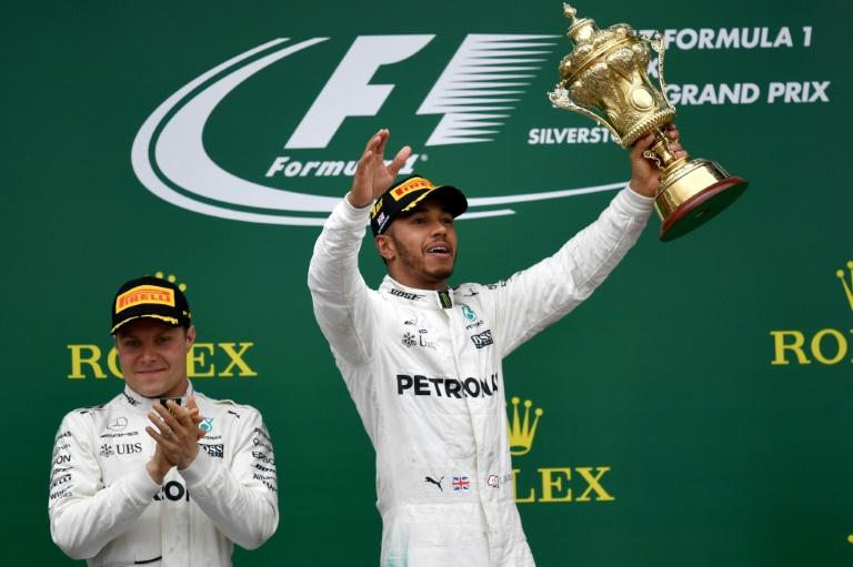 Mercedes' British driver Lewis Hamilton (right) celebrates next to second-placed Mercedes' Finnish driver Valtteri Bottas after winning the British Formula One Grand Prix in Silverstone on July 16, 2017