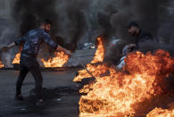 A man rides his scooter as an anti-government protester sets fire to tires to block a road, during a protest in Beirut, Lebanon, Tuesday, March 2, 2021. Scattered protests broke out in different parts of Lebanon Tuesday after the Lebanese pound hit a record low against the dollar on the black market, a sign of the country's multiple crises deepening with no prospects for a new Cabinet in the near future. (AP Photo/Hassan Ammar)