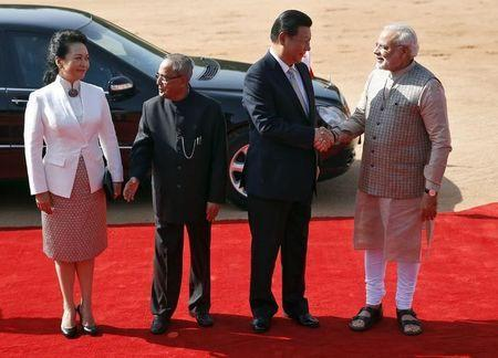 India's Prime Minister Narendra Modi (R) and China's President Xi Jinping (2nd R) shake hands as Xi's wife Peng Liyuan and India's President Pranab Mukherjee (2nd L) look on during Xi's ceremonial reception at the forecourt of India's Rashtrapati Bhavan presidential palace in New Delhi September 18, 2014. REUTERS/Ahmad Masood