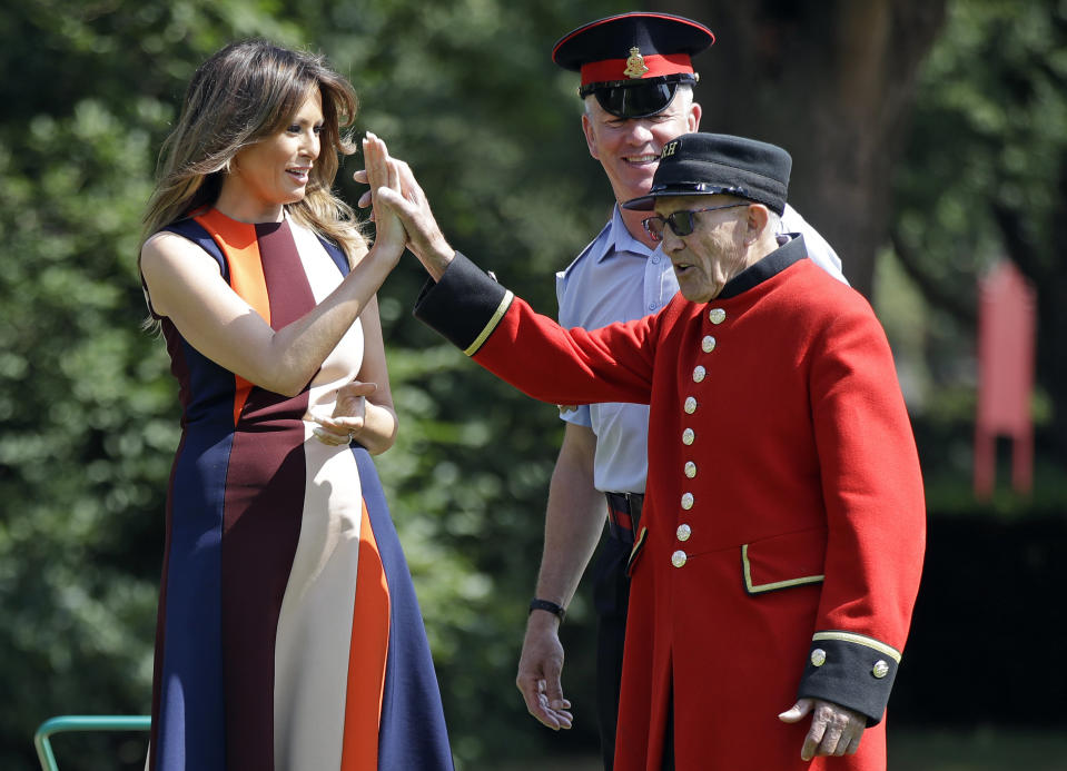 US First Lady Melania Trump, high-fives with a Chelsea Pensioner as she tries her hand at bowls during a visit to the Royal Hospital, Chelsea, London.