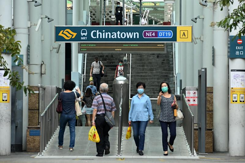 People walk in and out of the Singapore Mass Rapid Transit station in the Chinatown district in Singapore on June 12, 2020, as the city state eased its partial lockdown restrictions aimed at curbing the spread of the COVID-19 coronavirus. (Photo by ROSLAN RAHMAN / AFP) (Photo by ROSLAN RAHMAN/AFP via Getty Images)