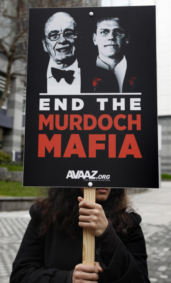 A protesters holding a placard with pictures of Rupert Murdoch, left, and his son James, as they stage a rally, outside the headquarters of News International in London, Friday, Feb. 17, 2012. News Corp. chief executive Rupert Murdoch gave staff at his scandal-hit tabloid The Sun new assurances over their future Friday in London crisis talks. Staff said Murdoch had discussed plans to open a new Sunday tabloid and confirmed that workers currently suspended amid police inquiries into alleged wrongdoing would be allowed to return to their posts. (AP Photo/Lefteris Pitarakis)