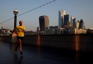 FILE PHOTO: A man runs at sunrise, with the City of London financial district in the background