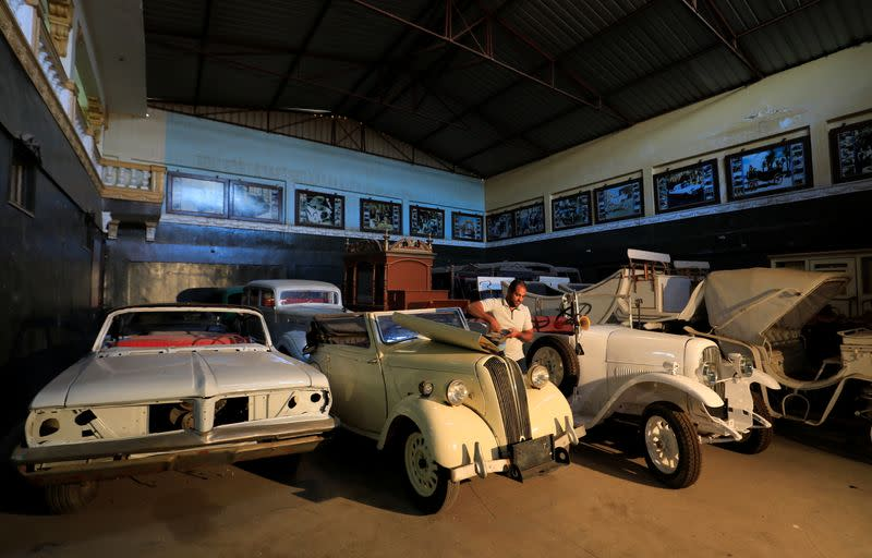 Ayman Sima, the 38-years-old son of Sayed Sima, an Egyptian collector of vintage cars, checks the battery of a British Standard Flying Eight Tourer - 1948 automobile at his father's store, in the Giza suburb of Abu Rawash