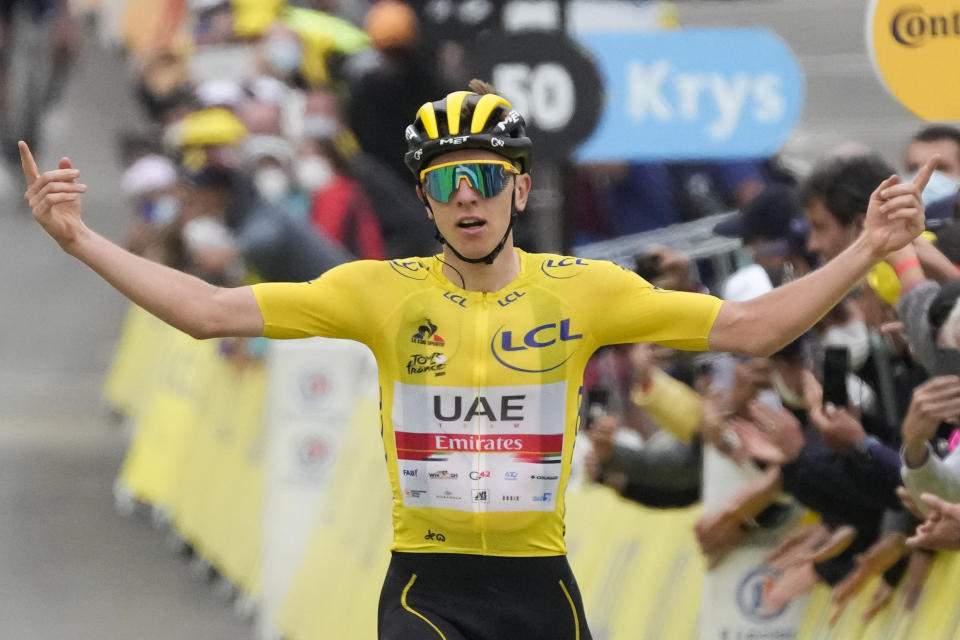 Slovenia's Tadej Pogacar, wearing the overall leader's yellow jersey, celebrates as he crosses the finish line to win the eighteenth stage of the Tour de France cycling race over 129.7 kilometers (80.6 miles) with start in Pau and finish in Luz Ardiden, France,Thursday, July 15, 2021. (AP Photo/Christophe Ena)