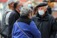 People wearing face masks walk down a street in Saint Jean de Luz, southwestern France, Wednesday, Oct.28, 2020. France is bracing for a potential new lockdown as the president prepares a televised address Wednesday aimed at stopping a fast-rising tide of virus patients filling French hospitals and a growing daily death toll. French markets opened lower on expectations that President Emmanuel Macron will announce some kind of lockdown Wednesday.(AP Photo/Bob Edme)