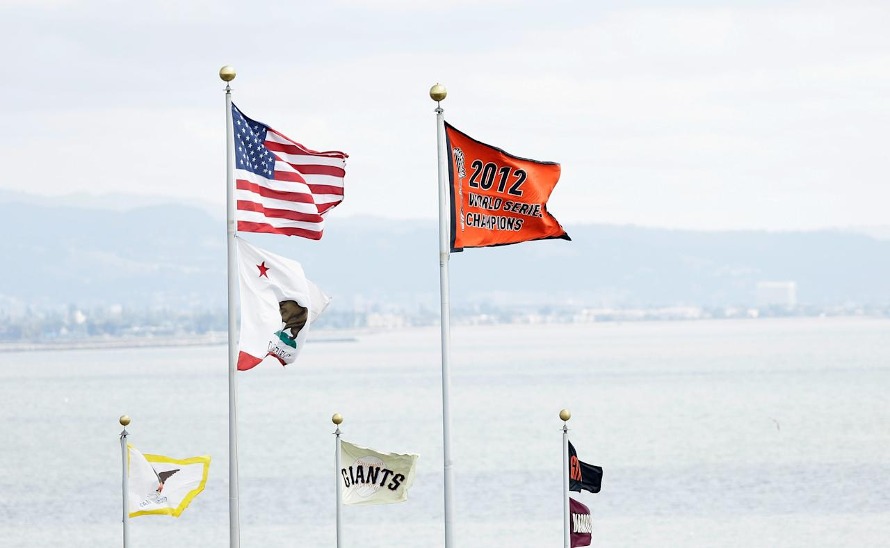 SAN FRANCISCO, CA - APRIL 05:  The 2012 Championship Banner flies next to the American Flag before the San Francisco Giants home opener against the St. Louis Cardinals at AT&T Park on April 5, 2013 in San Francisco, California.  (Photo by Ezra Shaw/Getty Images)
