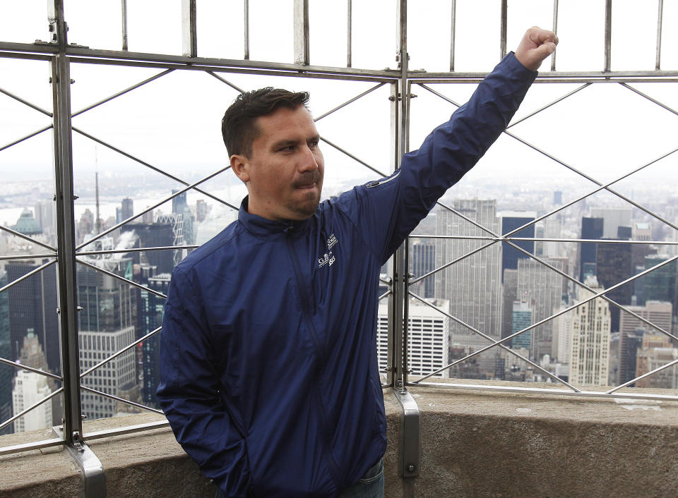 Rescued Chilean miner Edison Pena raises his arm in salute at the Empire State Building in New York, November 5, 2010. Pena plans to run the New York City Marathon on Sunday, less than a month after he was rescued from a collapsed mine that trapped him and 32 companions for 69 days. REUTERS/Shannon Stapleton   (UNITED STATES - Tags: DISASTER SPORT ATHLETICS SOCIETY)