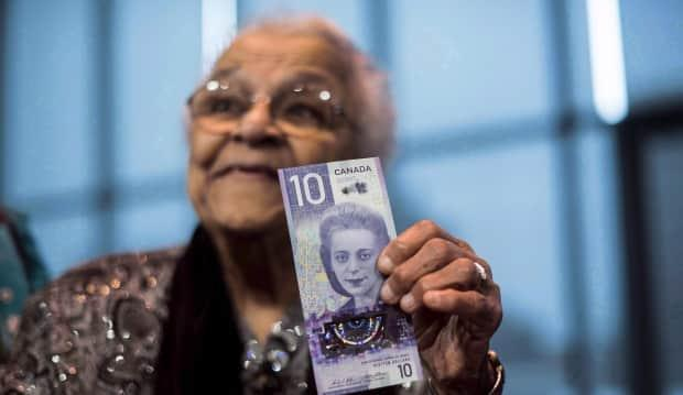 Wanda Robson, sister of Viola Desmond, holds a $10 bank note featuring Desmond during a press conference in Halifax in 2018. A new school in Ontario will bear Desmond's name. (Darren Calabrese/The Canadian Press - image credit)