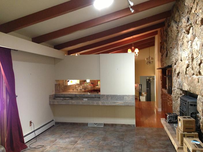 """<div class=""""caption""""> <strong>BEFORE</strong>: Laura and Scott were both raised in midcentury homes, which drew them to this one, and they were set on keeping its original 17-foot moss rock wall. """"It's a double-sided fireplace, but there was a stove on the other side that made it so you couldn't see through,"""" Laura says. </div> <cite class=""""credit"""">Laura Arledge</cite>"""