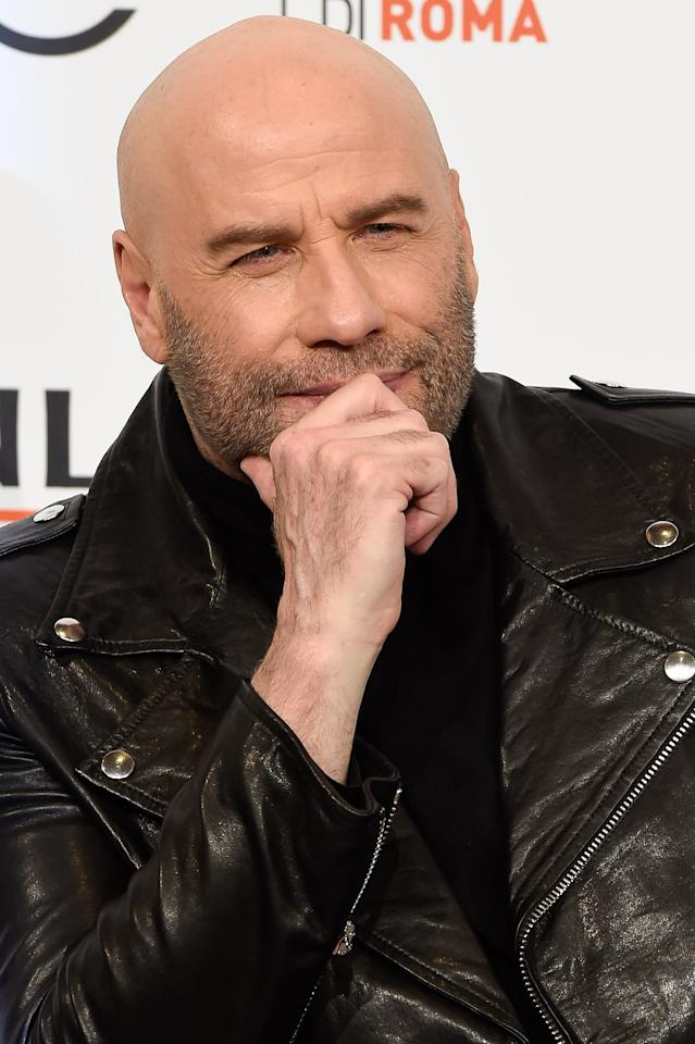 John Travolta is doing what all of us do—or should do—when we finally land on a truly perfect grooming look: put it on a silver platter with a wardrobe of black and more black.