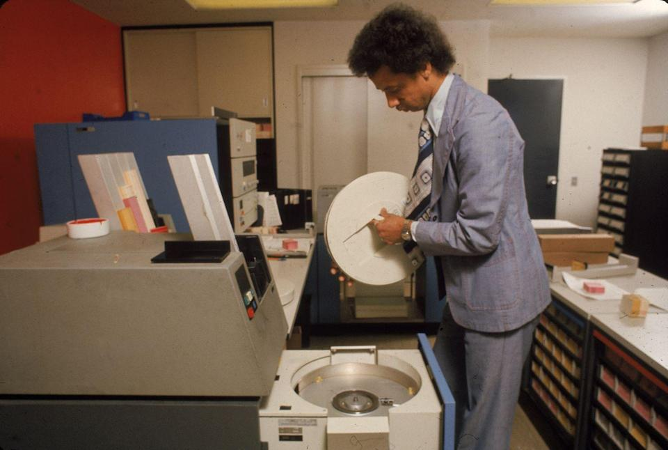 <p>In 1975, an employee replaces the a computer's magnetic tape data storage drive. It seems like an arduous job, but it was one of the frequent tasks required to keep the early computer models running smoothly. </p>