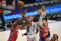 Washington Wizards guard Bradley Beal (3) goes to the basket past against Philadelphia 76ers center Joel Embiid (21) and forward Danny Green (14) during the first half of an NBA basketball game Friday, March 12, 2021, in Washington. (AP Photo/Nick Wass)