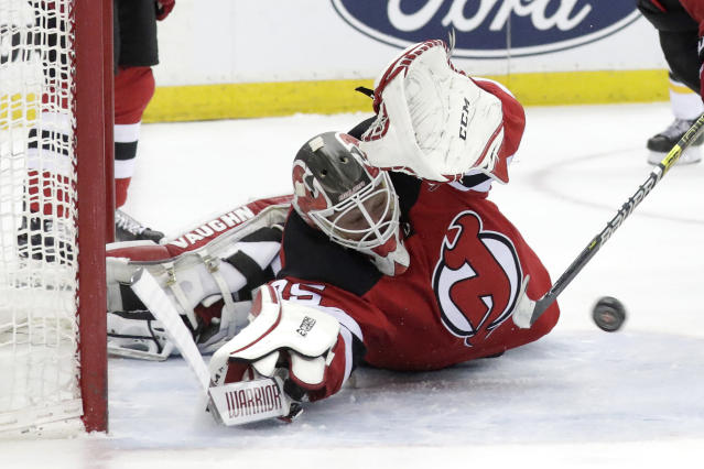 New Jersey Devils goaltender Cory Schneider tries to stop a scoring shot by Boston Bruins center Patrice Bergeron during the first period of an NHL hockey game Thursday, March 21, 2019, in Newark, N.J. (AP Photo/Julio Cortez)