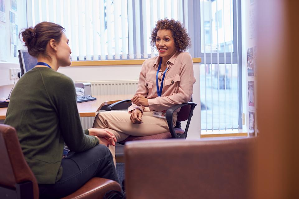 Female College Student Meeting With Campus Counselor Discussing Mental Health Issues