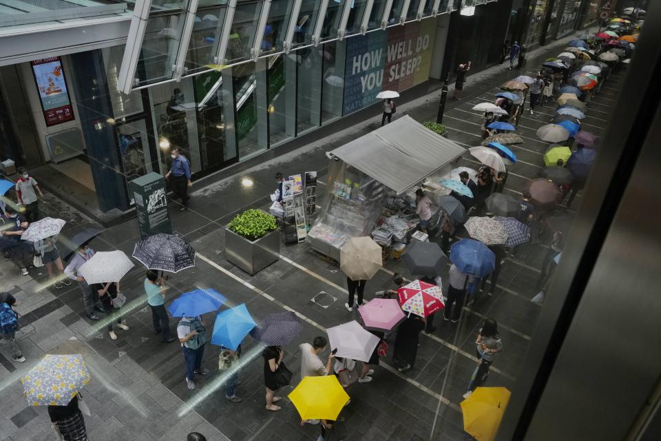 People queue up for last issue of Apple Daily at a newspaper booth at a downtown street in Hong Kong, Thursday, June 24, 2021. Hong Kong's sole remaining pro-democracy newspaper has published its last edition. Apple Daily was forced to shut down Thursday after five editors and executives were arrested and millions of dollars in its assets were frozen as part of China's increasing crackdown on dissent in the semi-autonomous city. (AP Photo/Vincent Yu)
