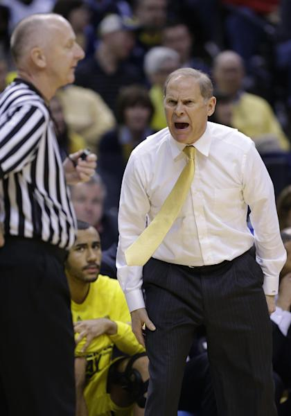 Michigan head coach John Beilein, right, argues a call with an official in the first half of an NCAA college basketball game against Michigan State in the championship of the Big Ten Conference tournament on Sunday, March 16, 2014, in Indianapolis. (AP Photo/Michael Conroy)