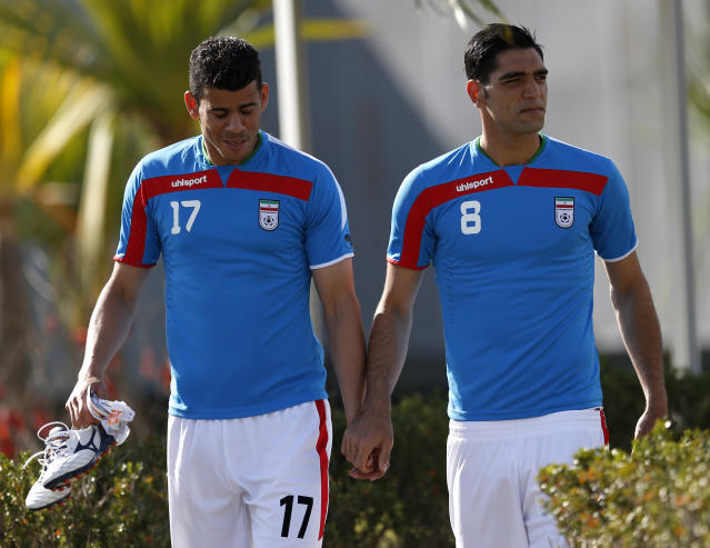 Iran's national soccer team players Mohammad Khanzadeh, left, and Sardar Azmoon hold hands while walking toward the pitch for warm ups before an international soccer friendly against Trinidad and Tobago at the Corinthians soccer team training center Sao Paulo, Brazil, on Sunday, June 8, 2014. Iran will play in group F of the 2014 soccer World Cup. (AP Photo/Julio Cortez)