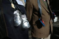 """People with baby shoes tied with black ribbons hanging from their neck, symbolizing the children who died in """"mother and baby homes"""", the homes where children were exiled for the shame of having been born to unwed mothers, protest in Dublin ahead of the visit of Pope Francis, in Dublin, Ireland, Saturday, Aug. 25, 2018 . The pontiff is traveling to Ireland for a two-day visit. (Aaron Chown/PA via AP)"""