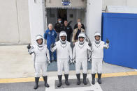 NASA astronauts, from left, Shannon Walker, Victor Glover, Mike Hopkins and Japan Aerospace Exploration Agency (JAXA) astronaut Soichi Noguchi, right, wearing SpaceX spacesuits, stop to pose for a picture as walk out of the Neil A. Armstrong Operations and Checkout Building to depart for Launch Complex 39A during a dress rehearsal Thursday, Nov. 12, 2020, at NASA's Kennedy Space Center in Cape Canaveral, Fla., for a scheduled Nov. 14 launch to the International Space Station (Joel Kowsky/NASA via AP)