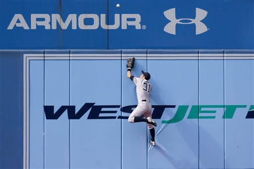 New York Yankees' Ichiro Suzuki, of Japan, climbs the wall as he watches a homerun by Toronto Blue Jays' Rajai Davis' during the first inning of a baseball game in Toronto, Saturday, Sept. 29, 2012. (AP Photo/The Canadian Press, Chris Young)