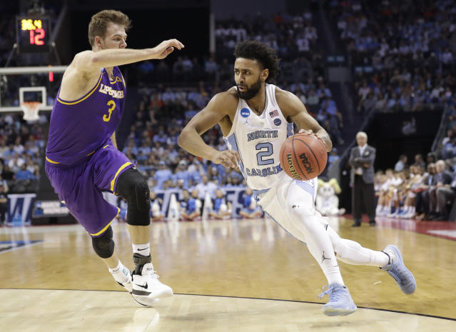 North Carolina's Joel Berry II (2) drives against Lipscomb's Michael Buckland (3) during the first half of a first-round game in the NCAA men's college basketball tournament in Charlotte, N.C., Friday, March 16, 2018. (AP Photo/Gerry Broome)