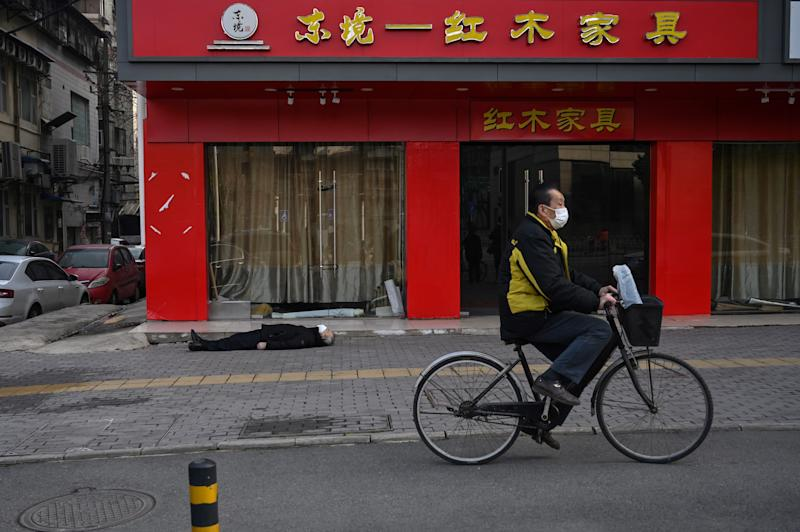 EDITORS NOTE: Graphic content / This photo taken on January 30, 2020 shows a man wearing a facemask cycling past an elderly man collapsed and died on the pavement along a street near a hospital in Wuhan. - AFP journalists saw the body on January 30, not long before an emergency vehicle arrived carrying police and medical staff in full-body protective suits. The World Health Organization declared a global emergency over the new coronavirus, as China reported on January 31 the death toll had climbed to 213 with nearly 10,000 infections. (Photo by Hector RETAMAL / AFP) / TO GO WITH China-health-virus-death,SCENE by Leo RAMIREZ and Sebastien RICCI (Photo by HECTOR RETAMAL/AFP via Getty Images)