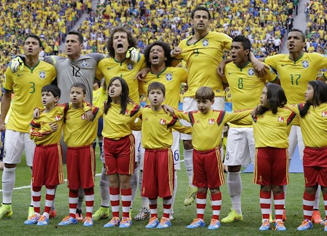 Brazil's Thiago Silva, goalkeeper Julio Cesar, David Luiz, Marcelo, Fred, Paulinho and Luiz Gustavo, from left, sing the national anthem prior to the group A World Cup soccer match between Cameroon and Brazil at the Estadio Nacional in Brasilia, Brazil, Monday, June 23, 2014. (AP Photo/Andre Penner)