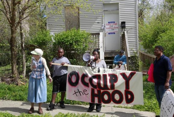 "Vanessa Spark (L), a member of Occupy Cincinnati and Occupy the Hood addresses the crowd in front of a foreclosed home during a Occupy Cincinnati march in Cincinnati, Ohio March 24, 2012. Occupy activists across America say they have found a cause that represents an issue for the ""99 percent"" and embodies the movement's anti-Wall Street message: helping struggling homeowners fight foreclosure and eviction. Picture taken March 24, 2012."