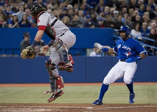 Toronto Blue Jays right fielder Rajai Davis, right, gets by Boston Red Sox catcher Jarrod Saltalamacchia, left, at home plate to score a run during second-inning baseball game action in Toronto, Friday, April 5, 2013. Blue Jays' Mark DeRosa hit a sacrifice fly on the play. (AP Photo/The Canadian Press, Nathan Denette)