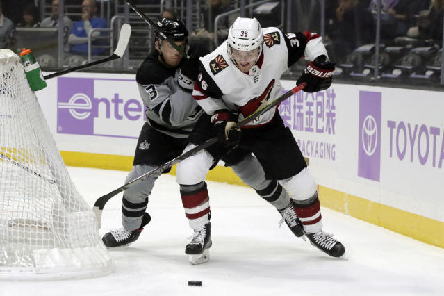Arizona Coyotes right wing Christian Fischer, right, battles Los Angeles Kings defenseman Matt Roy, left, for the puck during the first period of an NHL hockey game in Los Angeles, Saturday, Nov. 23, 2019. (AP Photo/Alex Gallardo)