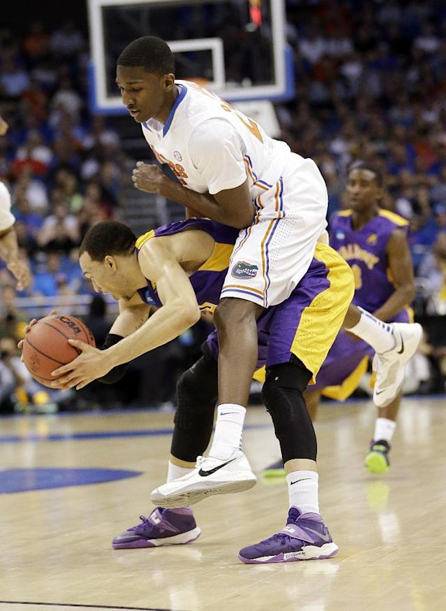 Florida forward DeVon Walker (25) goes over Albany forward Gary Johnson (20) during the first half in a second-round game in the NCAA college basketball tournament Thursday, March 20, 2014, in Orlando, Fla. (AP Photo/John Raoux)