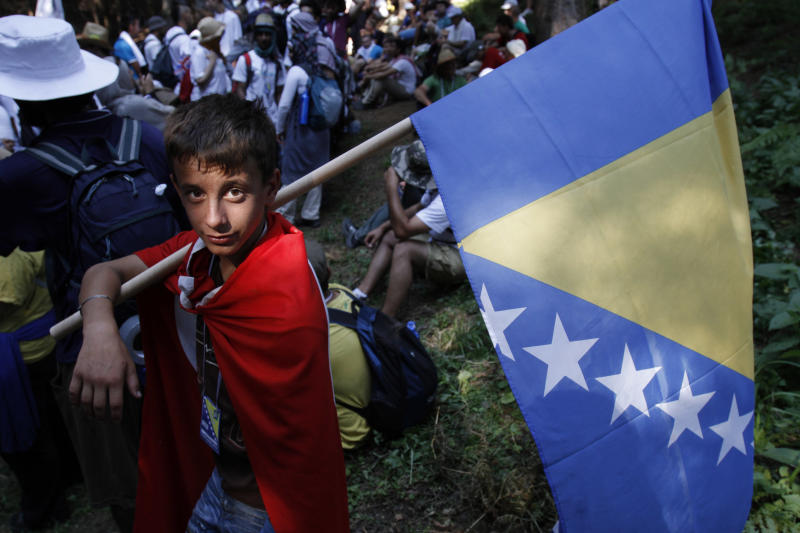 """Bosnian boy Armin Gerovic, 14, a participant of the """"March of Peace"""" poses with the Bosnian flag before the start of the march near the village of Nezuk, 150 km north east of Sarajevo, Bosnia, Sunday, July 8, 2012. Several thousand people, including survivors of Europe's worst massacre since World War II, started a 110-kilometer march from Nezuk to Srebrenica, following the path along which Muslims fled Serb forces at Srebrenica 17 years ago.(AP Photo/Amel Emric)"""