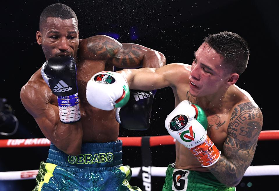 Robson Conceicao (L) and Oscar Valdez (R) exchange punches during their fight for the WBC super featherweight championship at Casino del Sol on Sept. 10, 2021 in Tucson, Arizona. (Photo by Mikey Williams/Top Rank Inc via Getty Images)