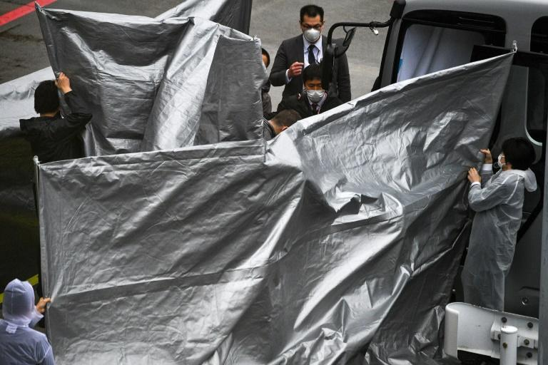 Officials held up silver plastic sheets to shield the arriving Taylors from cameras at Narita airport