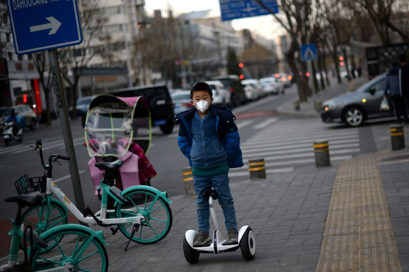 Child wearing a face mask rides a smart self-balancing scooter on a street, as the country is hit by an outbreak of the novel coronavirus, in Beijing