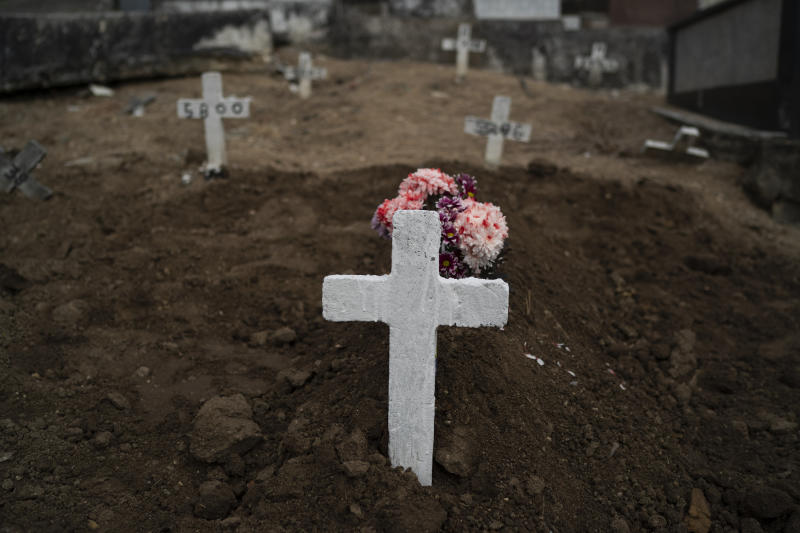 "A cross marks the grave of Ana Maria, a 56-year-old nursing assistant who died from the new coronavirus, in Rio de Janeiro, Brazil, Tuesday, April 28, 2020. Ana Maria's daughter Taina dos Santos said that the situation in the Salgado Filho public hospital where her mother worked is complicated and that some health workers have to buy their own protective gear. ""She gave everything to her job until the very end,"" said the 27-year-old daughter. (AP Photo/Leo Correa)"