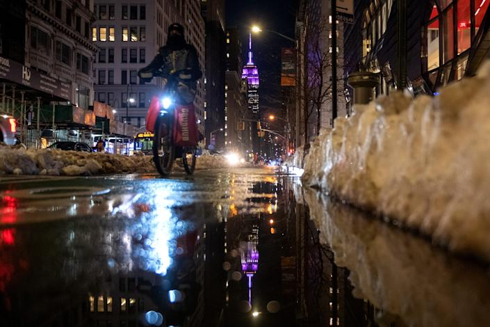 A Grubhub delivery driver rides near the Empire State Building lit up in purple in honor of World Cancer Day on February 04, 2021 in New York City.
