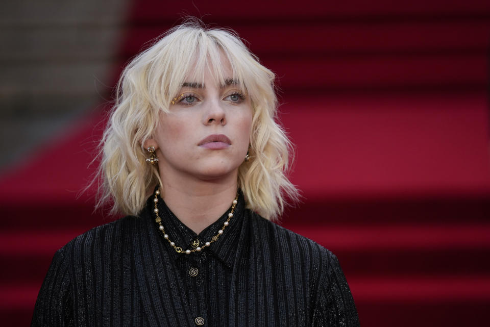 Billie Eilish poses for photographers upon arrival for the World premiere of the new film from the James Bond franchise 'No Time To Die', in London Tuesday, Sept. 28, 2021. (AP Photo/Matt Dunham)