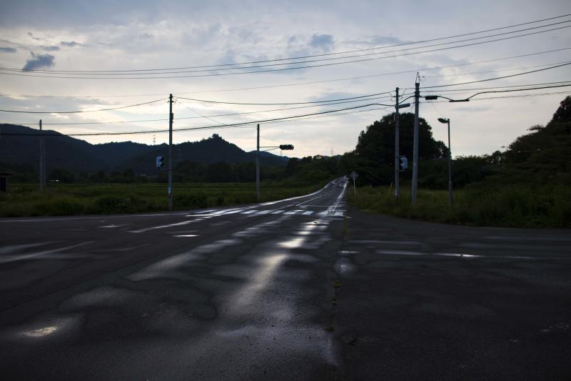 In this July 10, 2011 photo, an abandoned street stretches through the town of Naraha, inside the 20-kilometer (12-mile) exclusion zone around the Fukushima Dai-ichi nuclear plant, in northeastern Japan. A year after a tsunami crippled the plant and caused widespread radiation leaks, a massive and complex cleanup has begun, but experts say areas inside the nuclear exclusion zone will be difficult to decontaminate. (AP Photo/David Guttenfelder)