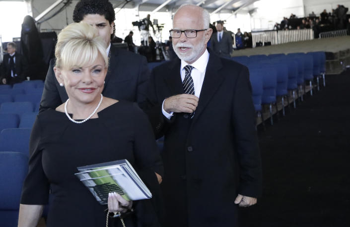 FILE - In this March 2, 2018 file photo, Televangelist Jim Bakker, right, walks with his wife Lori Beth Graham after a funeral service at the Billy Graham Library for the Rev. Billy Graham, in Charlotte, N.C. Jim Bakker and his southwestern Missouri church will pay restitution of $156,000 to settle a lawsuit that accused the TV pastor of falsely claiming that a health supplement could cure the coronavirus. Missouri court records show that a settlement agreement was filed Tuesday, June 22, 2021. (AP Photo/Chuck Burton File)