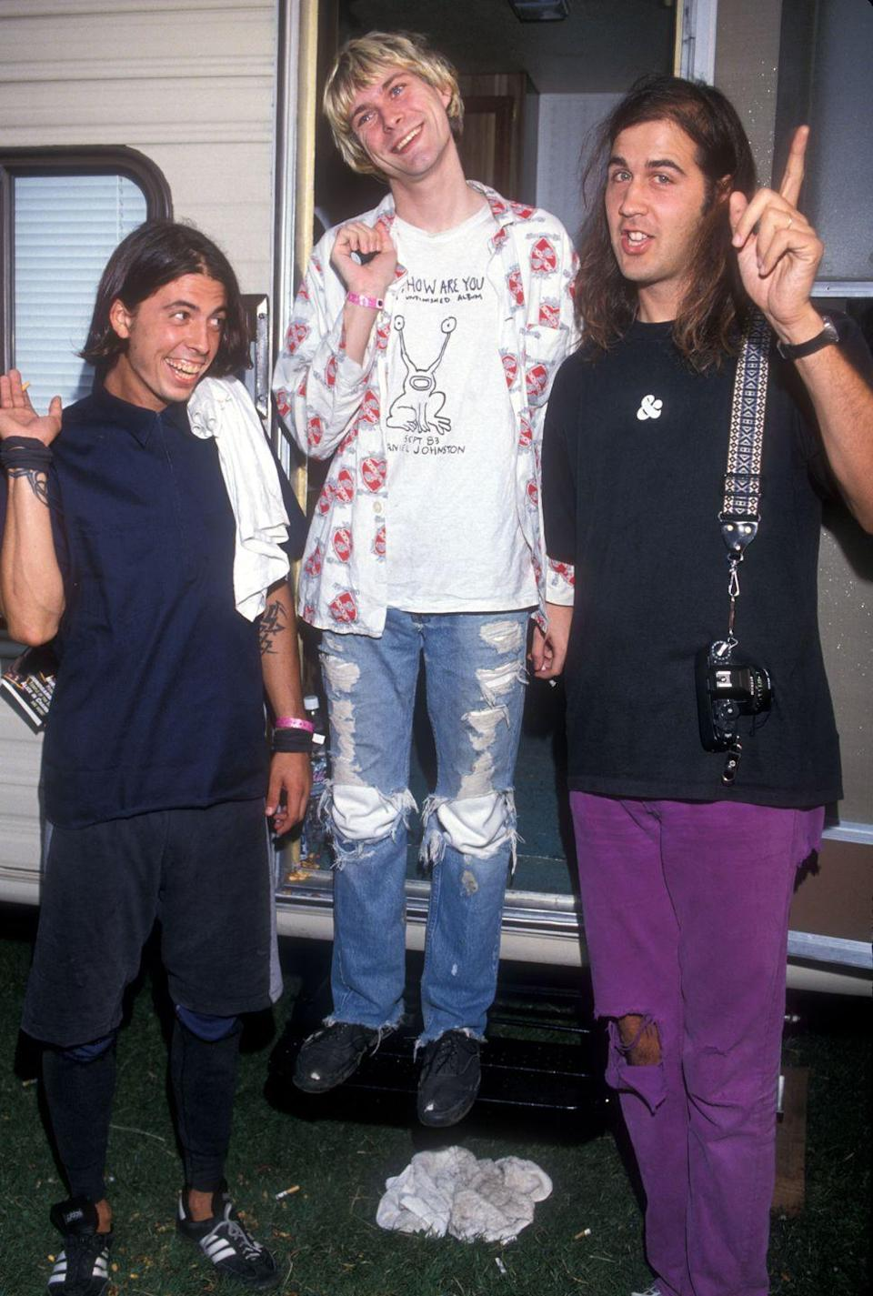 <p>Kurt Cobain, Dave Grohl, and Krist Novoselic of Nirvana emerge from an RV at the 1992 MTV VMA awards. </p>