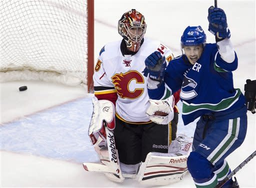 Calgary Flames goalie Henrik Karlsson (35) looks on as Vancouver Canucks center Maxim Lapierre (40) celebrates teammate Vancouver Canucks defenseman Marc-Andre Gragnani's, not shown, goal during third period NHL hockey action at Rogers Arena in Vancouver, British Columbia, Saturday, March, 31, 2012. (AP Photo/The Canadian Press, Jonathan Hayward)