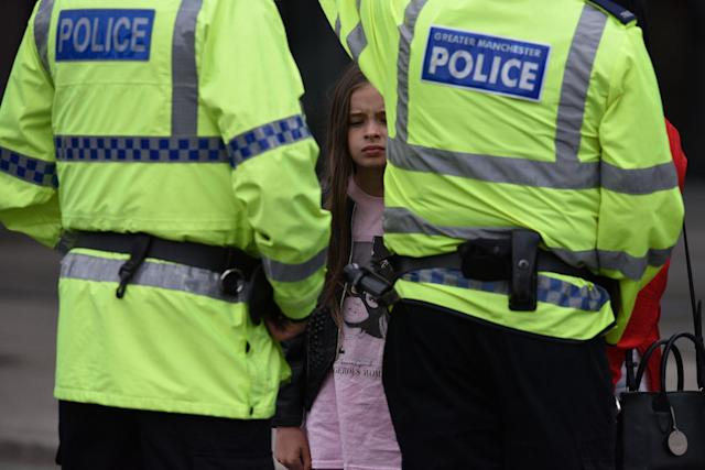 <p>A woman and a young girl wearing a t-shirt of U.S. singer Ariana Grande talks to police near Manchester Arena following a deadly terror attack in Manchester, northwest England on May 23, 2017. (Oli Scarff/AFP/Getty Images) </p>