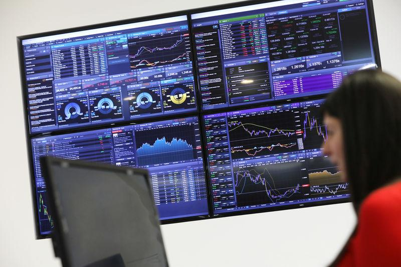 A trader works as a screen shows market data behind her at CMC markets in London